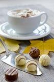 Pralines et une tasse de cappuccino Image libre de droits