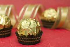 Pralines and gold ribbon Royalty Free Stock Photos