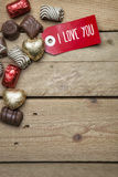 Pralines and red sign I love you on wooden background Royalty Free Stock Photography