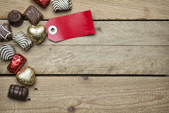 Pralines and red sign on wooden background Royalty Free Stock Photo