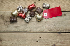 Pralines and red sign on wooden background Royalty Free Stock Images