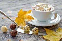 Pralines, une tasse de cappuccino et feuilles d'automne Photos libres de droits