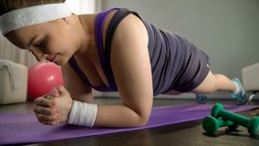 Pralle Dame, die in Plankenposition, große Motivation habend steht, um Gewicht zu verlieren lizenzfreies stockfoto