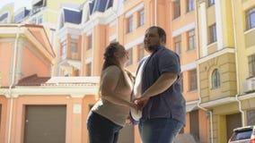 Pralle Frau, die Freund auf Backe während des romantischen Datums, ersten Schritt unternehmend küsst stock video footage