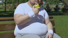 Praller Fleisch fressender Apfel und Sitzen auf Bank, gesunder kalorienarmer Imbiss, Diät stock footage