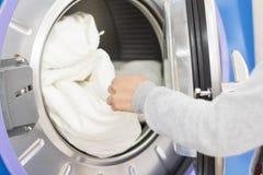 Pralniana pralka Ręka stawia niektóre łóżkowych prześcieradła lub dostaje od pralnianej pralki lub w obrazy royalty free