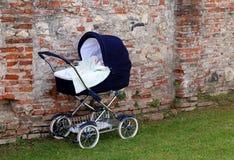 Pram dla nowonarodzonych dzieci na ogródzie i ścianie Zdjęcie Royalty Free