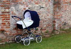 Pram for newborn babies on the garden and the wall royalty free stock photo