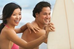 Prancha asiáticas dos pares da mulher do homem que surfam na praia Fotografia de Stock
