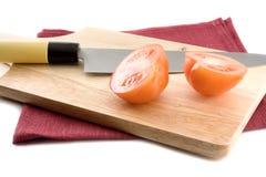 A prancha de madeira com uma faca e os tomates. Fotos de Stock Royalty Free