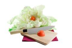 A prancha de madeira com uma faca e os tomates. Fotografia de Stock Royalty Free