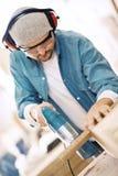 A prancha de madeira do corte do homem que usa o gabarito bonde viu Fotografia de Stock