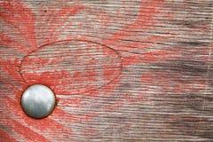 A prancha de madeira envelhecida textured o fundo com tampão do metal e pintura vermelha Vista macro Foto de Stock Royalty Free