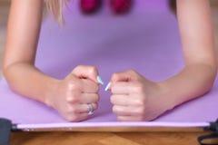 Prancha fêmea nova do cotovelo do treinamento na esteira roxa da aptidão ou da ioga imagens de stock royalty free