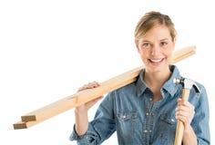 Pranchas de madeira de With Hammer And do trabalhador da construção no ombro foto de stock