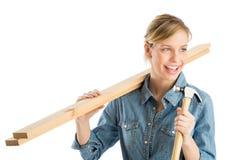 Pranchas de madeira de Holding Hammer And do trabalhador da construção no ombro imagem de stock royalty free