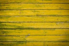 Pranchas pintadas de madeira verde-amarelas velhas abstraia o fundo fotos de stock