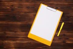 Prancheta com a folha branca no fundo de madeira Vista superior fotografia de stock royalty free