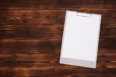 Prancheta com a folha branca no fundo de madeira Vista superior imagem de stock royalty free