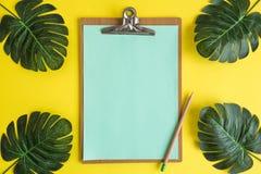 Prancheta com lápis e sumário verde das férias de verão das folhas imagens de stock