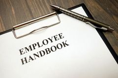 Prancheta com manual de empregado e pena na mesa fotografia de stock