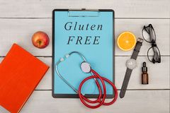 prancheta com texto & x22; Free& x22 do glúten; , livro, monóculos, relógio, fruto e estetoscópio imagem de stock royalty free