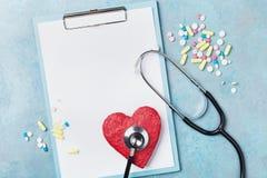 Prancheta da medicina, estetoscópio, comprimidos da droga, e forma vermelha do coração na opinião superior do fundo azul Conceito fotos de stock royalty free