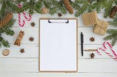 Prancheta e decoração vazias do Natal no fundo de madeira branco Configuração lisa, modelo da vista superior Para fazer foto de stock royalty free