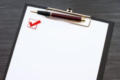 Prancheta preta com a folha de papel branca a pena e do metal isolada na tabela de madeira escura Caixa de seleção com um tiqueta foto de stock royalty free