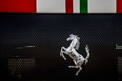 Prancing Horse Ferrari emblem. A chrome prancing horse Ferrari insignia under racing stripes on a fast sports car grille Royalty Free Stock Images