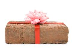 Prank gift. Red Brick Gift, Concept of joke, make fun of somebody, gift on April Fool's Day, Prank gift Royalty Free Stock Image