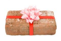 Prank gift. Red Brick Gift, Concept of joke, make fun of somebody, gift on April Fool's Day, Prank gift Royalty Free Stock Images
