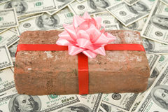 Prank gift and dollars. Red Brick Gift and dollars, Concept of joke, make fun of somebody, gift on April Fool's Day, Prank gift Royalty Free Stock Photo