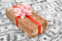 Prank gift and dollars. Red Brick Gift and dollars, Concept of joke, make fun of somebody, gift on April Fool's Day, Prank gift Stock Photos