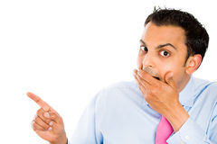 Prank, laughing man. Closeup portrait of handsome young businessman covering his mouth, laughing, and pointing at someone or something and looking at you, with Stock Image