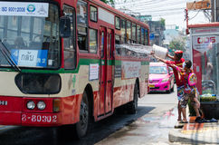 Pranking a bus. Bangkok, Thailand, 14 April 2015. A common sight during the annual Songkran water festival in Thailand, children wait by the road the splash Royalty Free Stock Images