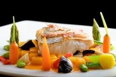 Pranzare fine, filetto di pesce bianco impanato in erbe e spezia con bacon arrostito fotografia stock