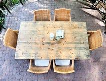 Pranzare tabella di legno con le presidenze di vimini Immagine Stock
