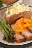 Pranzo affettato del porco con le pesche e la patata cotta fotografie stock libere da diritti