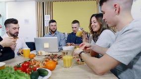 Pranzo dell'ufficio Il personale ha smantellato la pizza dalla tavola Intervallo di pranzo sul lavoro archivi video