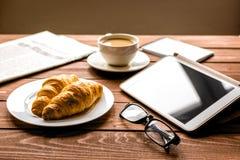 Pranzo dell'uomo d'affari a casa con caffè, croisant ed il dispositivo Immagine Stock Libera da Diritti