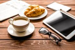 Pranzo dell'uomo d'affari a casa con caffè, croisant ed il dispositivo Immagine Stock
