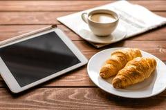 Pranzo dell'uomo d'affari a casa con caffè, croisant ed il dispositivo Fotografie Stock Libere da Diritti