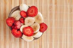 Pranzo di estate: tagli le banane e le fragole Immagini Stock