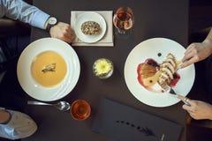 Pranzo di lavoro o cena in un ristorante le mani sulla tavola, piatti gradiscono la minestra e la carne, mangianti Vista superior immagini stock