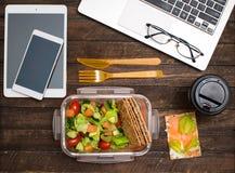 Pranzo di lavoro sano nel luogo di lavoro Le patatine fritte dell'insalata, del salmone, dell'avocado e del pane pranzano scatola immagini stock