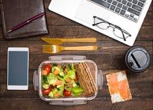 Pranzo di lavoro sano nel luogo di lavoro Le patatine fritte dell'insalata, del salmone, dell'avocado e del pane pranzano scatola immagine stock libera da diritti