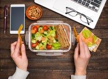 Pranzo di lavoro sano nel luogo di lavoro Le patatine fritte dell'insalata, del salmone, dell'avocado e del pane pranzano scatola fotografia stock libera da diritti