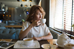 Pranzo piacevole della donna di affari in caffè dopo lavoro sulla sua compressa digitale Fotografia Stock