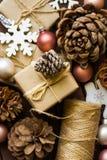 praparing和包裹圣诞节和新年gits的过程,自然材料,工艺纸,麻线,杉木锥体,木装饰品 免版税库存图片